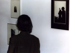 1990-Takemitsu next to a picture of himself in traditional Japanese dress taken in1969.