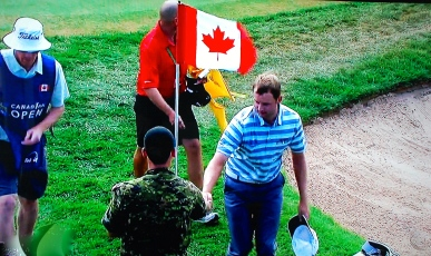 Professional golfer exiting the 18th green at Glen abbey during the Canadian OPen, shakes the hand of a Canadian military man.